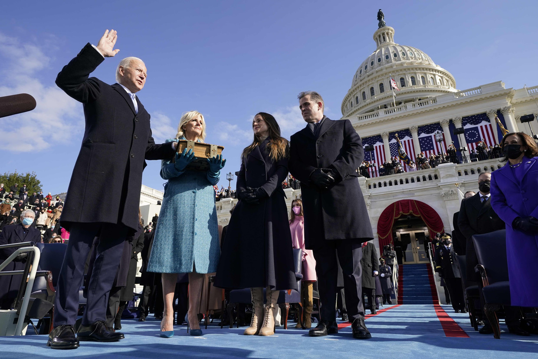 Joe Biden legt zijn hand op de bijbel die zijn vrouw Jill vasthoudt terwijl hij door rechter John Roberts (r) wordt beëdigd tot president. Naast het presidentiële paar hun kinderen Ashley en Hunter, in paarse jas vicepresident Kamala Harris. Beeld AFP