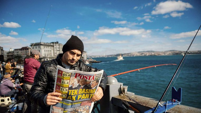 Een Turkse man leest in Istanboel een krant met verkiezingsuitslagen. Beeld afp
