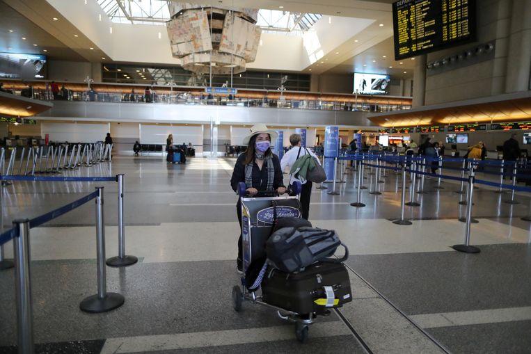 Een reiziger met een mondkapje op in de internationale terminal van luchthaven LAX in Los Angeles. Beeld REUTERS