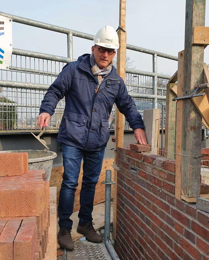Wethouder Johan Quik bij de kademuur in Schelluinen met daarin de vleermuissteen. Deze oogt een beetje als een brievenbus.