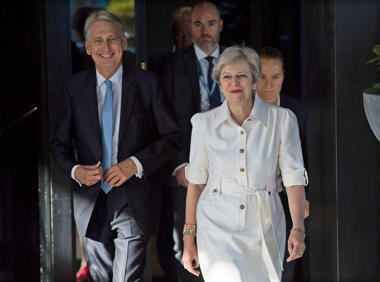 De Britse premier Theresa May en minister van Financiën Philip Hammond vanmorgen bij aankomst in Birmingham. Beeld EPA