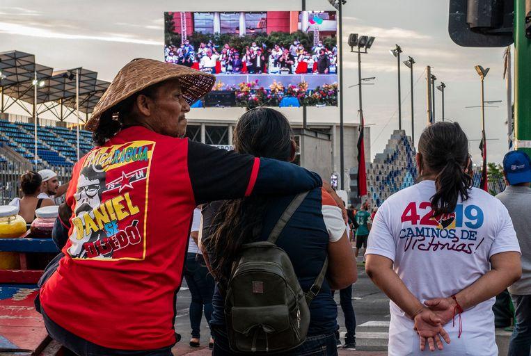 Aanhangers van de president van Nicaragua, Daniel Ortega, volgen een speech van hem in de hoofdstad Managua.  Beeld AFP