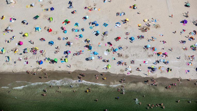 Luchtfoto van badgasten op het strand. Beeld anp