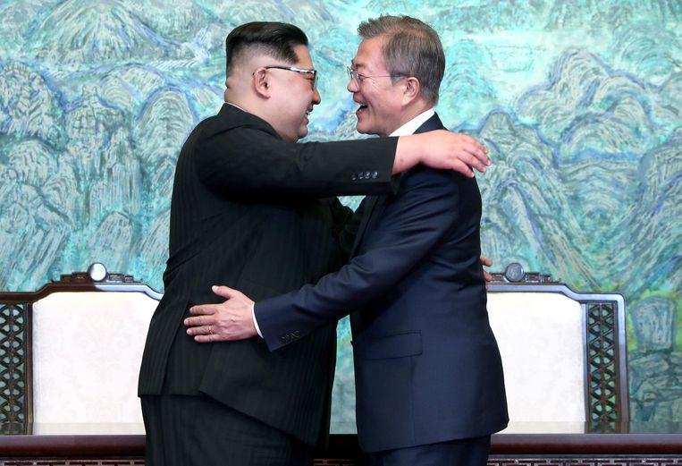 De Zuid-Koreaanse president Moon Jae-in (rechts) en de Noord-Koreaanse leider Kim Jong-un delen een toch wel hartelijke omhelzing in het Zuid-Koreaanse Panmunjom. Kim Jong-un is de eerste Noord-Koreaanse leider die de grens met het zuiden oversteekt sinds de oorlog van 1950-1953. Beeld Photo News