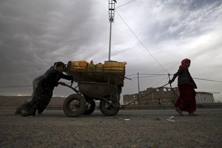 Op de vlucht geslagen kinderen transporteren water in het district Khamir. Beeld reuters