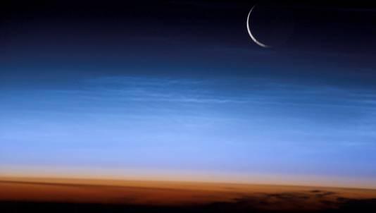 De zilverblauwe lichtende nachtwolken reiken tot ver boven de troposfeer. De troposfeer eindigt plotseling bij de tropopauze, de scherpe grens tussen de oranje- en blauwkleurige lagen van de atmosfeer