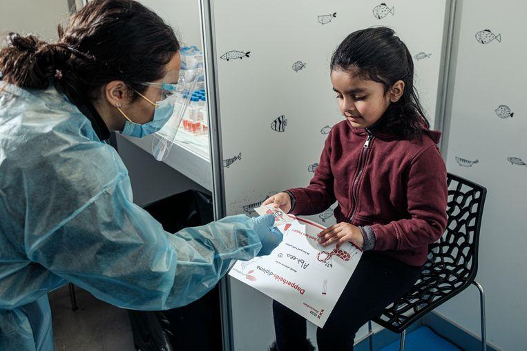 De kindertestbalie in de RAI. De 6-jarige Abheea Khan krijgt haar dapperheidsdiploma. Beeld Jakob van Vliet