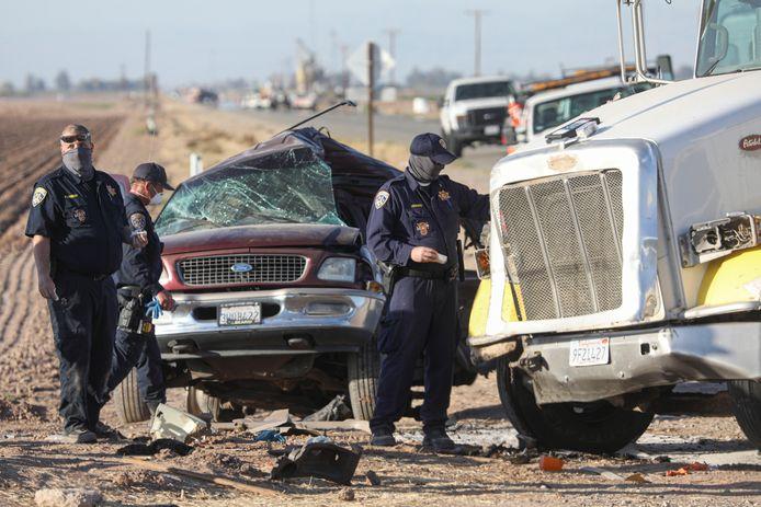 Agenten bij het wrak van de SUV waarin zeker 25 illegale migranten zaten gepropt. 13 van hen overleefden de crash niet.