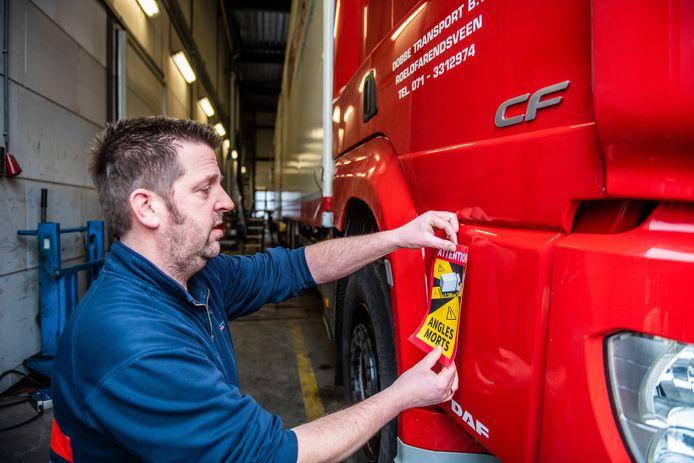 Peter Wesselius, werknemer bij Dobbe Transport uit Roelofarendsveen, brengt dodehoekstickers aan op vrachtwagens die naar Frankrijk rijden.