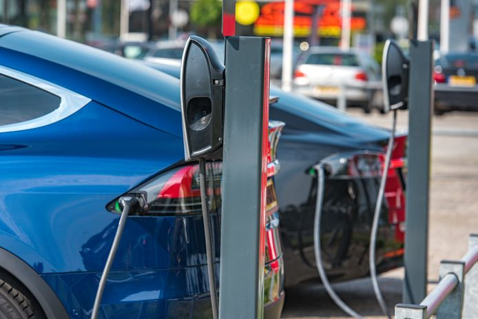 Twee Tesla's worden opgeladen. Bestuurders van de elektrische wagen zijn boete-kampioenen.