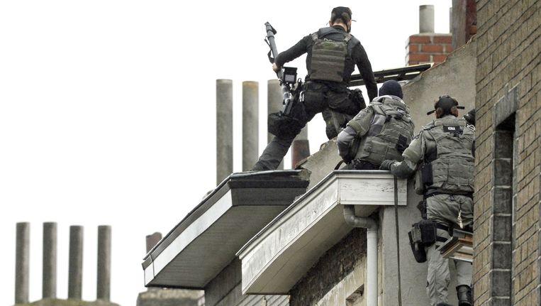 Speciale politie-eenheden op de daken van huizen in de deelgemeente Molenbeek. Beeld afp