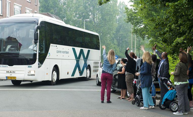 Ouders zwaaien hun kinderen uit als die vertrekken voor een schoolreisje. Beeld ANP