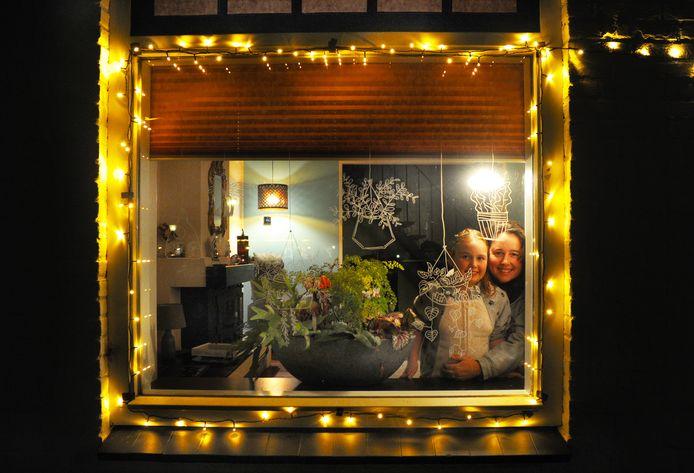 Ymke de Kater en Aimée (9) bij hun verlichte raam in Koudekerke.