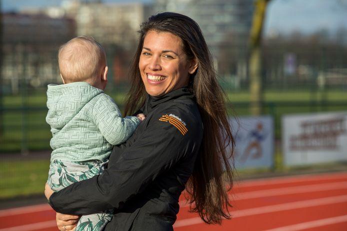 Esther Akihary poseert met haar zoon Sebastiaan op de atletiekbaan in Eindhoven.
