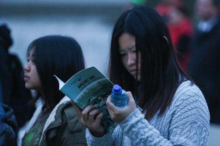 Eén van de aanwezigen zoekt wat achtergrond bij Anzac Day op.