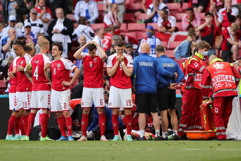 Een medisch team schiet de Deense voetballer Christian Eriksen te hulp nadat hij in elkaar is gezakt op het veld.