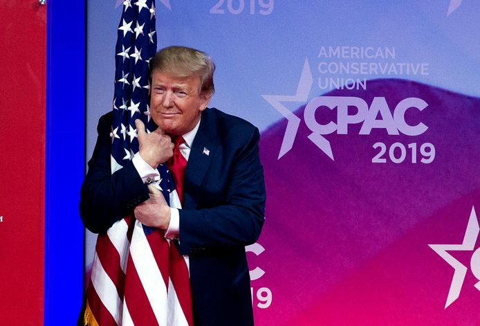 Trump omhelst de Amerikaanse vlag op de CPAC, een conferentie van conservatieve activisten.