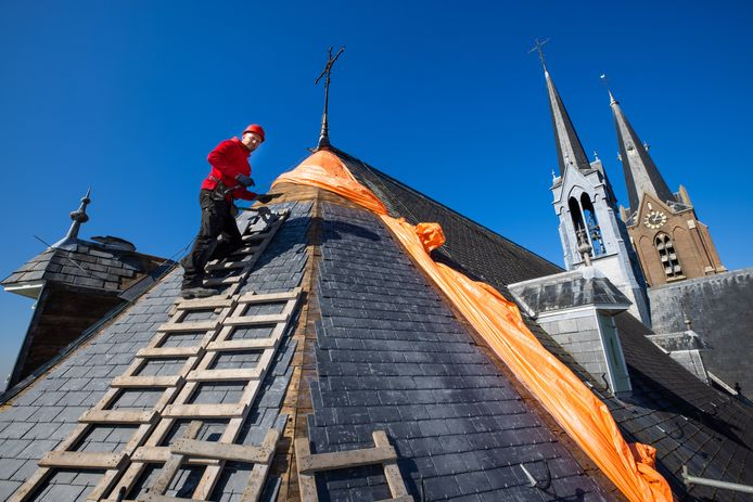 Marcel Sanders van leidekkersbedrijf  Van de Kimmenade BV vervangt de leien van de St. Jan Geboortekerk in Vlijmen.
