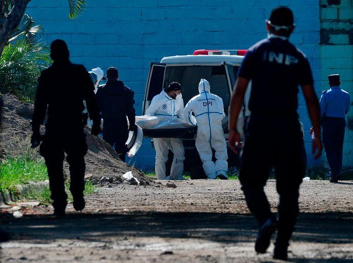 Het lichaam van een van de vermoorde gevangenen wordt door forensische onderzoekers meegenomen.