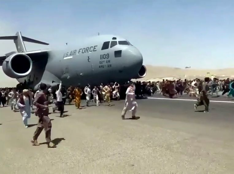 Honderden mensen renden maandag mee met een Amerikaans transportvliegtuig op de luchthaven van Kaboel. Het beeld is een van de symbolen geworden van de chaotische evacuatie. Beeld AP