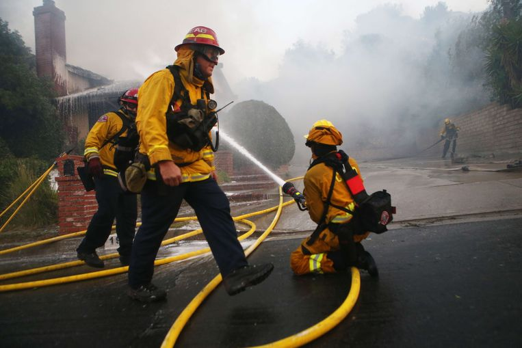 PORTER RANCH, CALIFORNIA - OCTOBER 11: Firefighters work at a house fire after dawn during the Saddleridge Fire on October 11, 2019 in Porter Ranch, California. The fast moving wind-driven fire has burned more than 7,500 acres and destroyed 25 structures.   Mario Tama/Getty Images/AFP == FOR NEWSPAPERS, INTERNET, TELCOS & TELEVISION USE ONLY ==