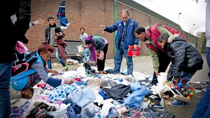 Vluchtelingen, bij sporthal Schuttersveld in Rotterdam-Crooswijk, zoeken kleding uit die door buurtbewoners is neergelegd.
