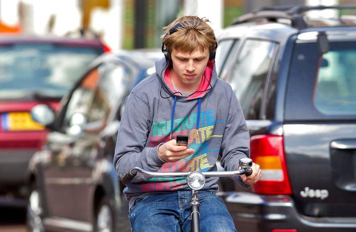 Telefoneren en muziek beluisteren tijdens het fietsen vergroten de kans op een ongeval.