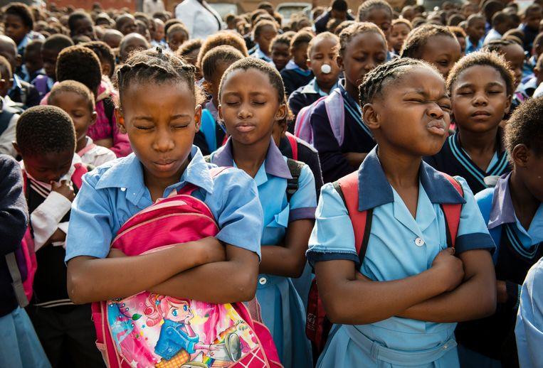 Schoolmeisjes bidden voor de start van de lessen van een school in Soweto. Beeld Bram Lammers