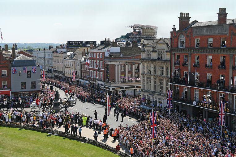Op de straathoek in Windsor staat het standbeeld van koningin Victoria, het jonge echtpaar is haar net voorbijgereden.  Beeld null