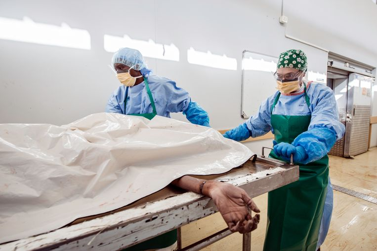 Forensisch patholoog Candice Hansmeyer (rechts) en onderzoeker Afrika Moloko (links) brengen een lichaam naar de autopsiezaal.  Beeld Bram Lammers
