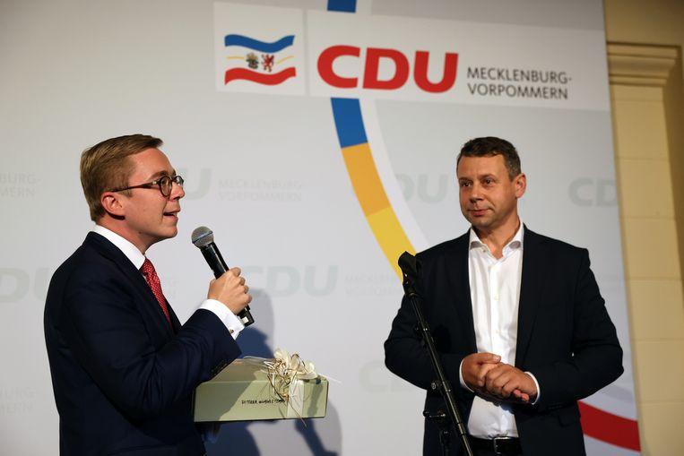 Uittredend Bondsdaglid Philipp Amthor (links) ontvangt een fles wijn, nadat hij niet is herkozen in het kiesdistrict 16, in deelstaat Mecklenburg-Vorpommern. Zijn plaats gaat naar de AfD. Beeld Christian Charisius/dpa