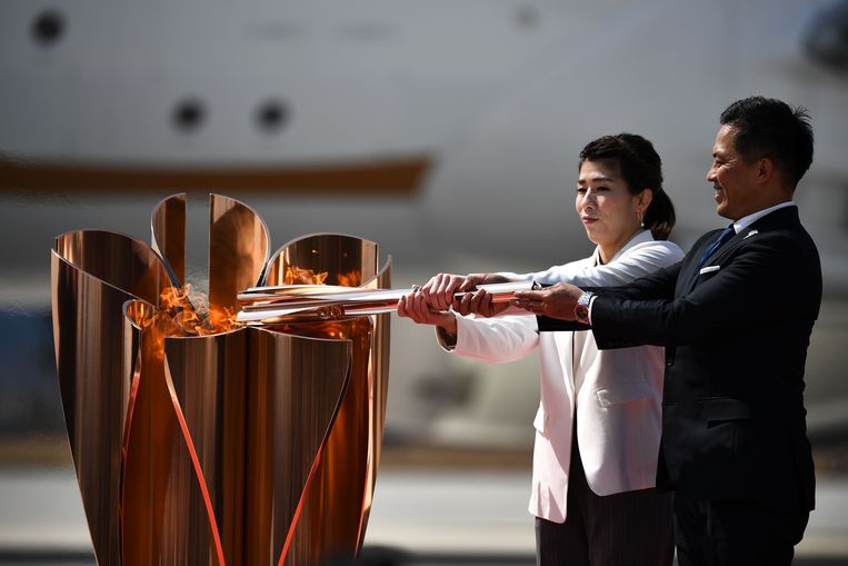 Saori Yoshida en Tadahiro Nomura lichten de olympische vlam.