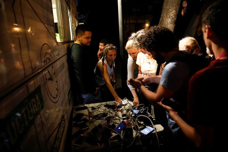 Mensen proberen hun mobiele telefoon op te laden aan een generator op een plein in Caracas. Beeld REUTERS