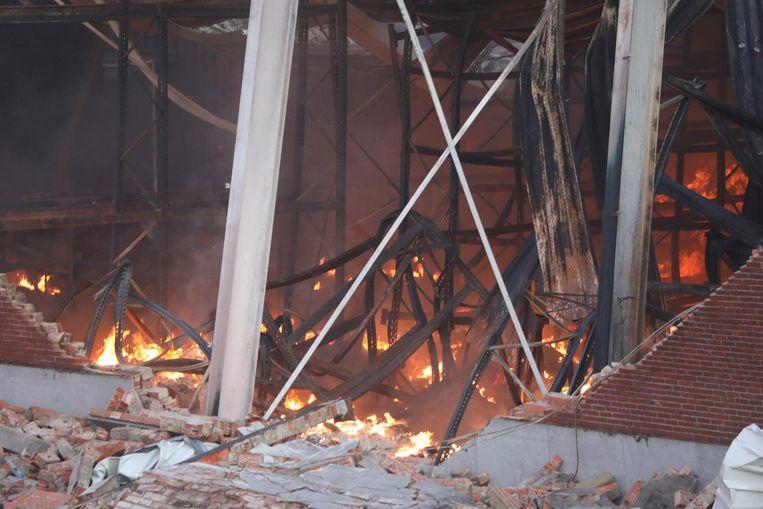 Smeulende brandhaardjes tussen verwrongen staal.