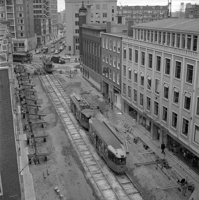 Onderhoud aan het wegdek en de trambanen in de Witte de Withstraat in 1959. We kijken richting de hoek Schiedamse Vest en Schilderstraat. Rechts het voormalige pand van kantoorboekhandel Blikman & Sartorius.