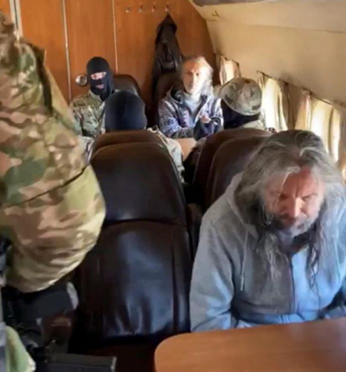 Twee van de drie gearresteerde mannen, waaronder Vissarion, in het gezelschap van gemaskerde agenten.