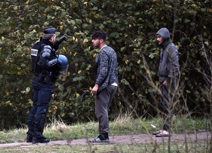 A French police speaks with migrants on October 23, 2018 during an operation to evacuate a migrant camp in Grande Synthe, northwestern France. - A migrant camp of 1.800 person has been evicted by French authorities near the French port city of Dunkirk, at Grande-Synthe, northwestern France, on October 23, 2018. (Photo by FRANCOIS LO PRESTI / AFP)