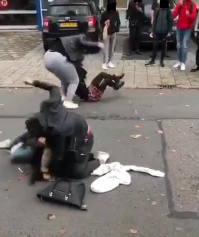 Meisjes halen uit naar meisjes die op straat liggen