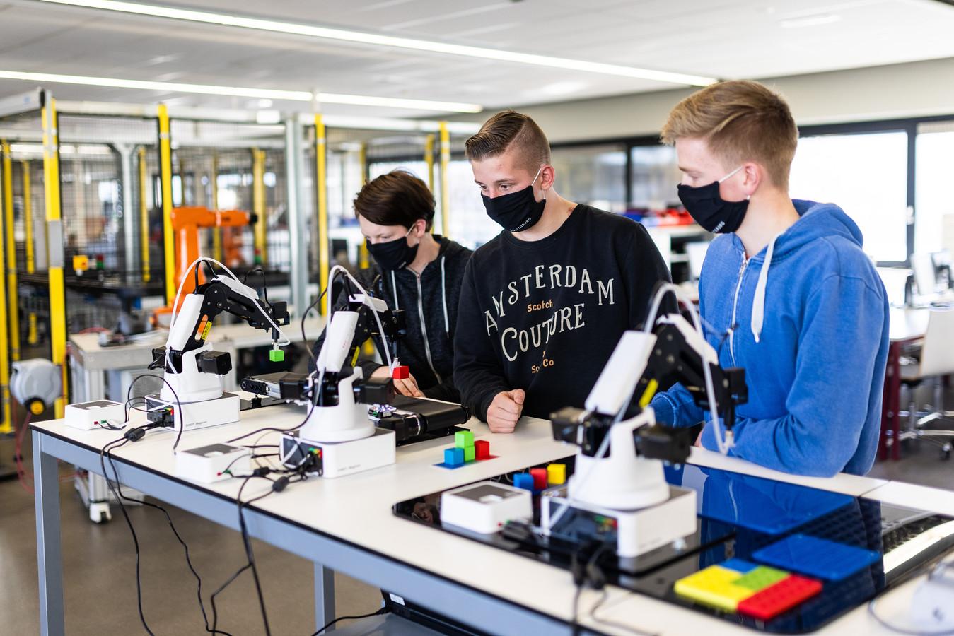 ROC-studenten Mechatronica Tjeerd, Dylan en Luc kijken geboeid naar de handelingen van de robots waarmee ze tijdens hun studie mee aan de slag mogen. Op de achtergrond de grote robotarm.
