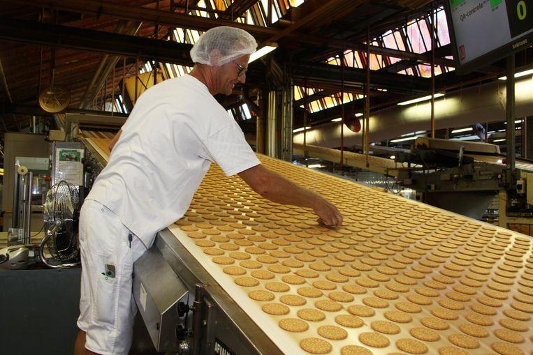 Een werknemer controleert de kwaliteit terwijl de Prince koeken afkoelen. Rechts de huidige verpakking. In de koek zelf staan een kroontje en een letter P gedrukt.