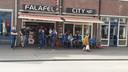 Supporters van Lech Poznan eten bij Falafel City.