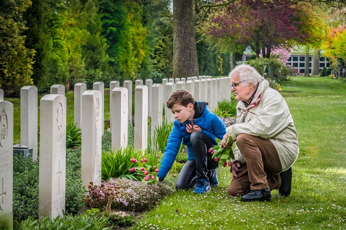 John Perik en kleinzoon Hugo bezoeken op de Oosterbegraafplaats het graf van een Britse soldaat, die op dag van de bevrijding van Enschede bij het ouderlijk huis van Perik om het leven kwam.