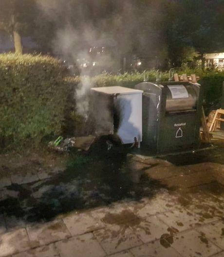 Brandweer blust brandend meubilair bij vuilcontainer