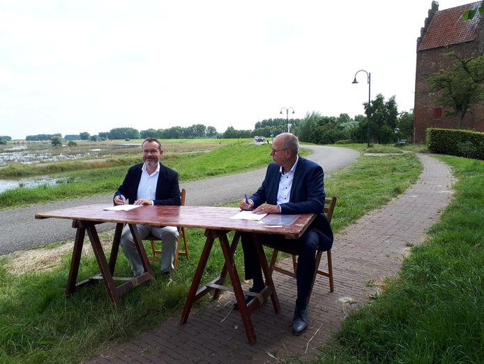 Dijkgraaf Mario Jacobs (links) en Boskalisdirecteur Maar van Oord ondertekenen de samenwerking voor de Meanderende Maas op de dijk bij Megen.