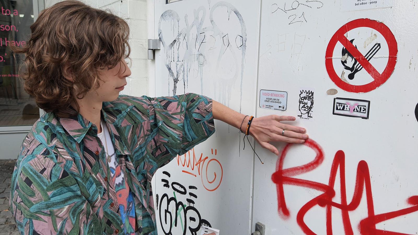 Kunstenaar Mees van de Voren plakt een van zijn bekende stickers