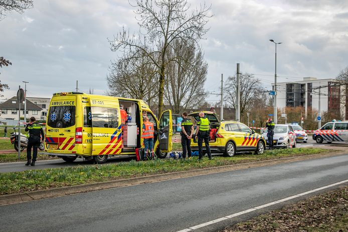 Ambulancepersoneel verzorgt het slachtoffer. Politie doet onderzoek.