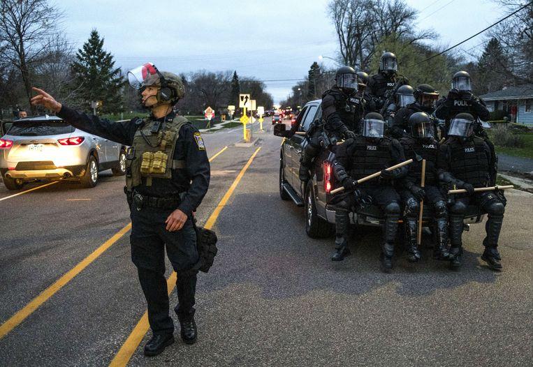 Een groep agenten in vechtuitrusting in Brooklyn Center, Minnesota. In de voorstad van Minneapolis heerst onrust nadat een zwarte automobilist is omgekomen bij een schietincident met de politie. Beeld AFP