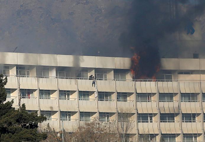 Een man probeert te vluchten van het balkon tijdens de aanval van gewapende mannen op Hotel Intercontinental in Kabul.