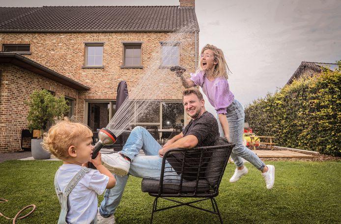 Michiel, Elise en hun zoontje Floris. Buiten spelen doet hij het liefst. Met de tuinslang in zijn handjes is hij helemaal in z'n element.