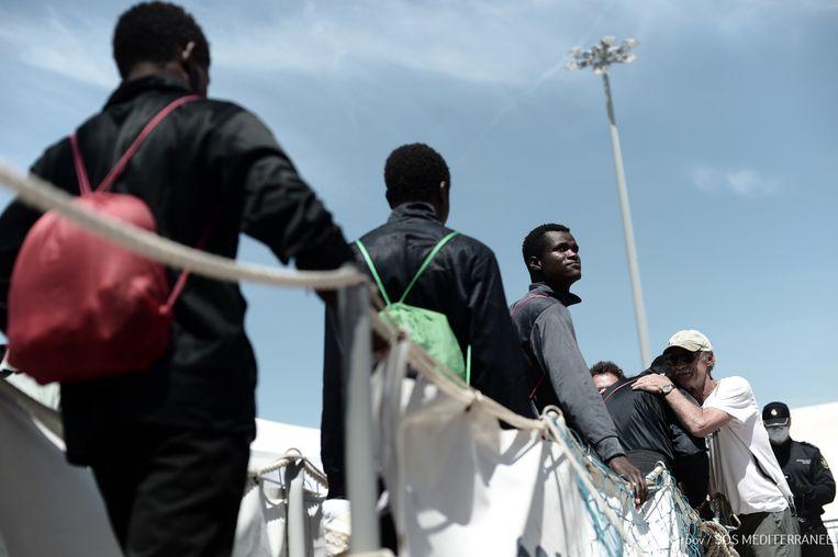 Enkele vluchtelingen stappen van het reddingsschip Aquarius dat aanmeert in Valencia. Beeld AFP